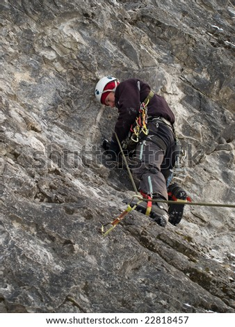 Male climber ascending vertical cliff face. Winter
