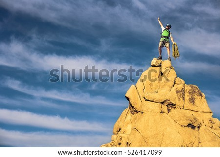 Male climber celebrates on the summit of a rock spire.
