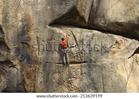 Male climber climbing rock face - stock photo