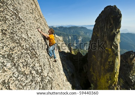 Male climber clings to a steep rock face. - stock photo