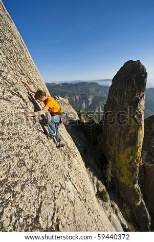 Male climber clings to a steep rock face.