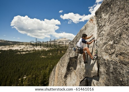 Male climber grips and scampers up a sheer rock wall in Yosemite's high Sierra Nevada mountains. - stock photo