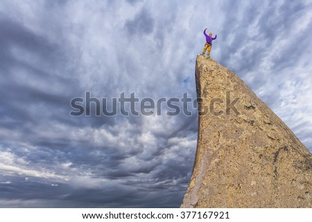 Male climber on the summit of the mountain. - stock photo