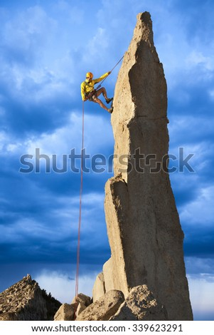 Male climber rappells from the summit of a sheer rock spire. - stock photo