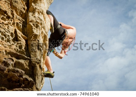 male climbing on sandstone cliff