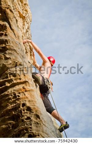 male climbing on sandstone cliff - stock photo