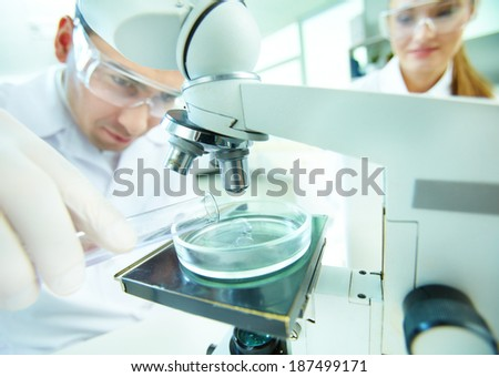 Male clinician studying chemical element in laboratory with his assistant near by - stock photo