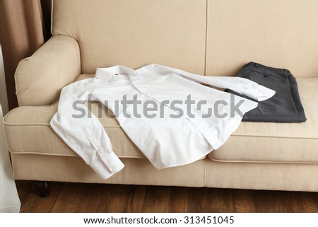Male clothing on sofa in room