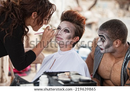 Male clown looking at woman getting makeup backstage - stock photo
