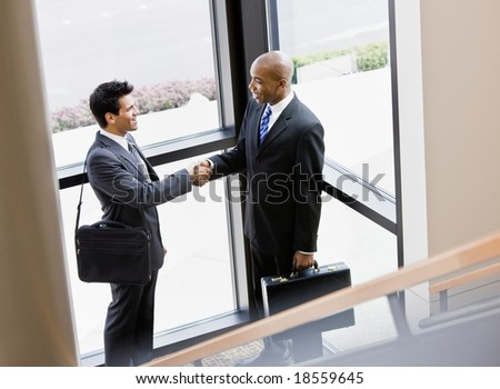Male co-workers shaking hands in corner of office building - stock photo