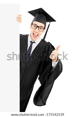 Male college graduate peeking behind blank panel and giving thumb up isolated on white background