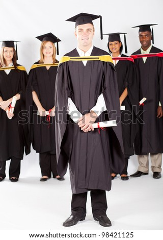 male college student at graduation with classmates - stock photo