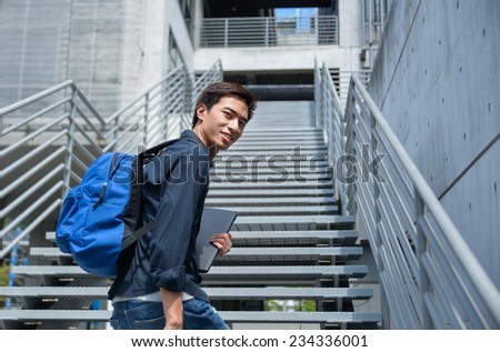 male college student holding laptop at campus - stock photo