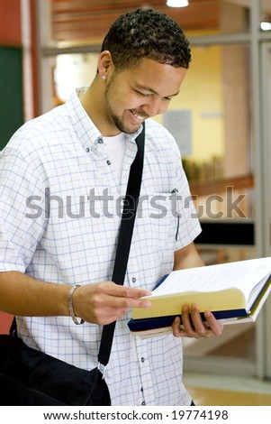 male college student reading a book in the passage