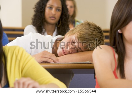 Male college student sleeping through a university lecture - stock photo