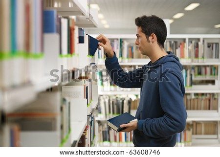 male college student taking book from shelf in library. Horizontal shape, side view, waist up - stock photo