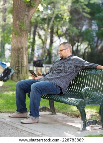 Male college student using digital tablet on bench at university campus
