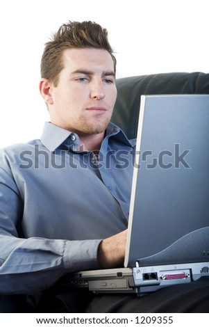 Male comfortably sitting in a sofa using a laptop