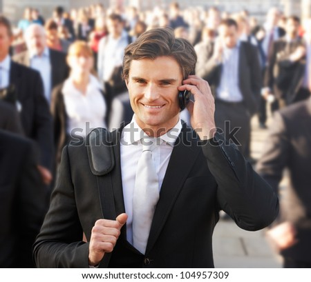 Male commuter in crowd using phone