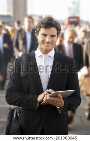Male commuter in crowd using tablet - stock photo