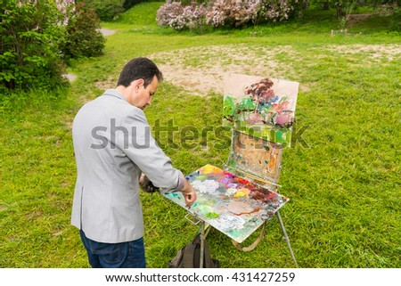 Male concentrated middle-aged creative artist mixing paint on a palette standing in front of a sketchbook during an art class in a forest - stock photo