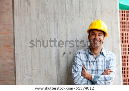 Male construction worker at a building site smiling - stock photo
