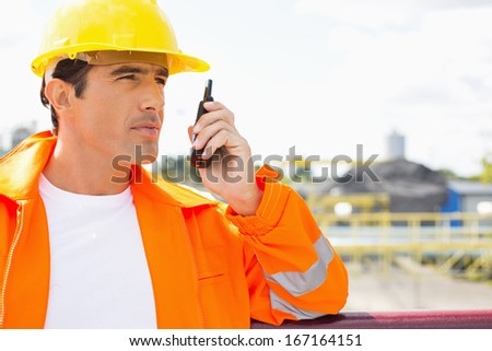Male construction worker communicating on two way radio at site - stock photo