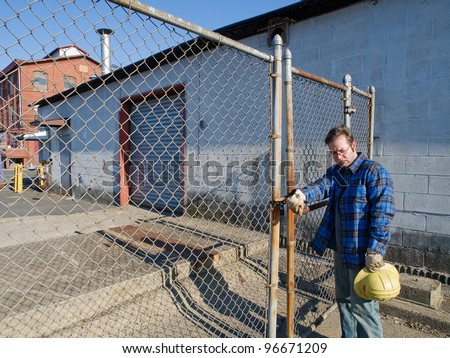 Male Construction Worker, forlorn, outdoors, out of work , locked out, factory - stock photo