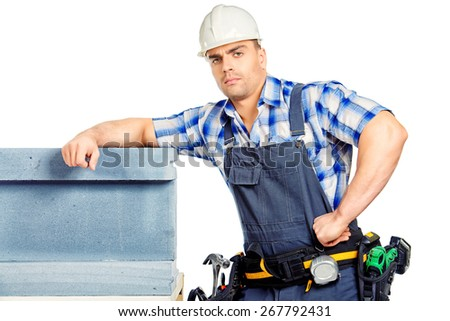 Male construction worker in working clothes, helmet and tools. Isolated over white. - stock photo