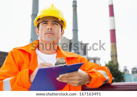 Male construction worker writing on clipboard at industry - stock photo