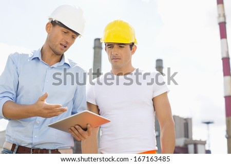 Male construction workers discussing over digital tablet at industry - stock photo