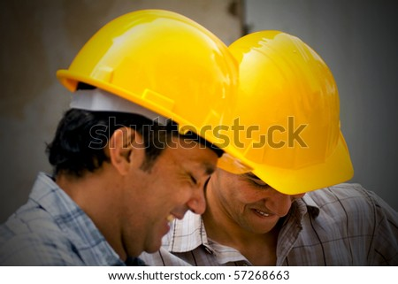 Male construction workers wearing helmets and smiling - stock photo