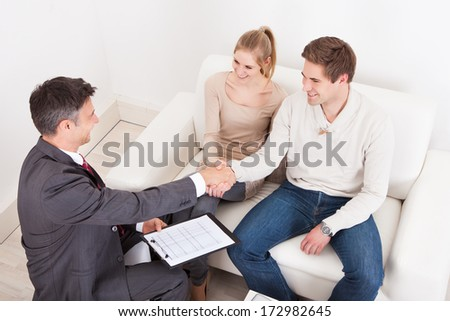 Male Consultant Shaking Hand With Young Couple At Home - stock photo