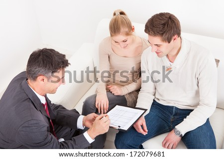 Male Consultant Showing Agreement To Young Couple At Home - stock photo
