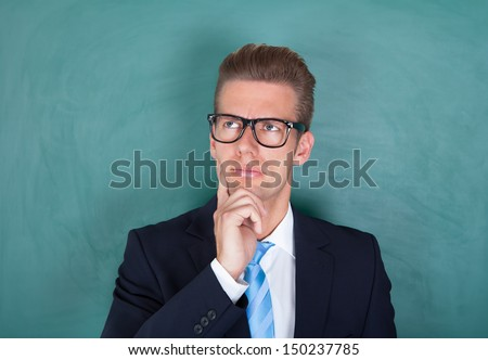 Male Contemplated Lecturer Standing In Front Of Chalkboard - stock photo