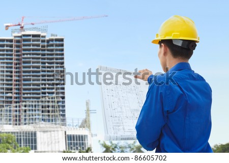 Male contractor or civil engineer looking at the building project on progress - stock photo