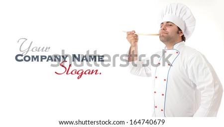 Male cook delightfully smelling the contents of a wooden spoon  - stock photo