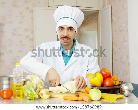 male cook in toque with vegetables  - stock photo