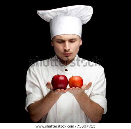 male cook in white uniform and hat with apples, black bckground - stock photo