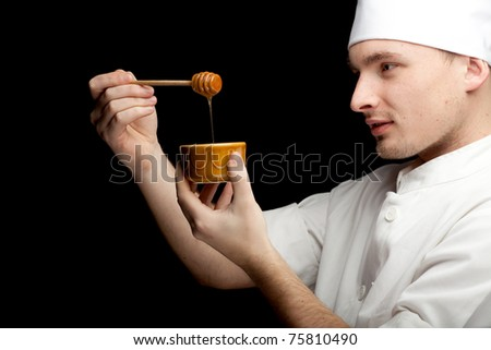 male cook in white uniform and hat with bowlof honey, black bckground