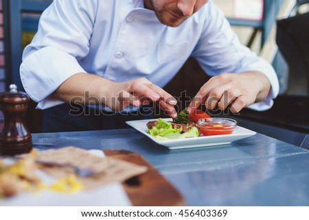 Male cook serve delicious steak on the cutting board at street cafe - stock photo