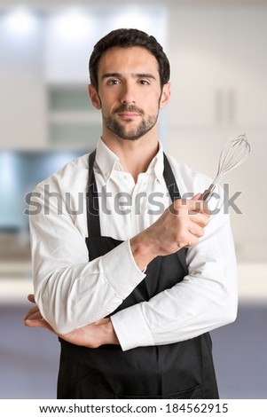 Male cooker with a black apron, smiling and holding a egg-beater, in a kitchen - stock photo