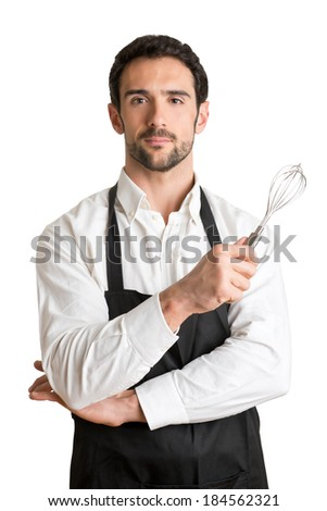 Male cooker with a black apron, smiling and holding a egg-beater, isolated in white - stock photo
