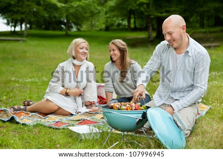 Male cooking food on bbq with friends in park - stock photo