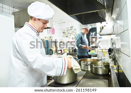 male cooks chef in uniform cooking at restaurant kitchen  - stock photo