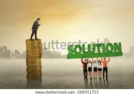 Male corporate leader standing on the stack of golden coins while giving command on his employees to bring a solution - stock photo