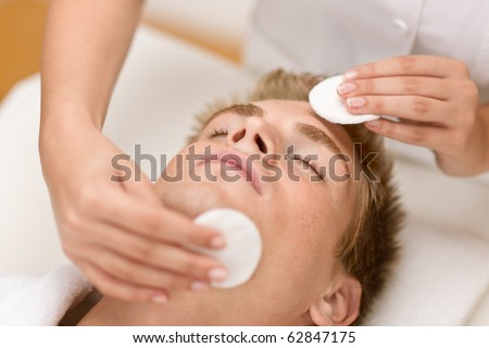 Male cosmetics - cleaning face treatment at luxury spa - stock photo