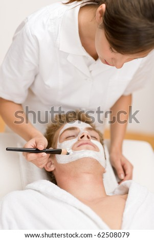 Male cosmetics - facial mask in luxury spa center - stock photo