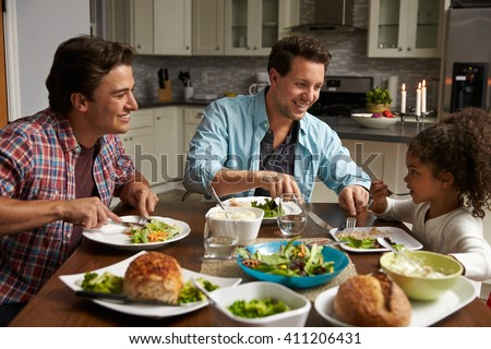 Male couple and black daughter dining in their kitchen - stock photo