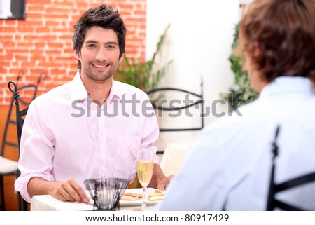 Male couple at restaurant - stock photo